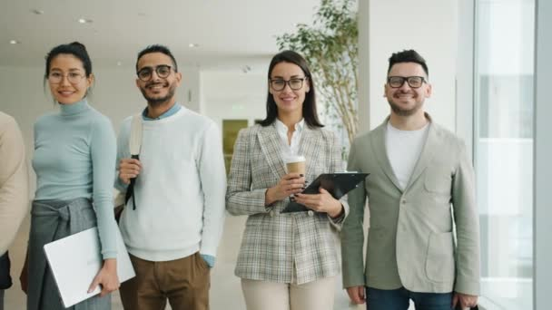 Portrait of multiracial team of professionals standing in lobby smiling looking at camera