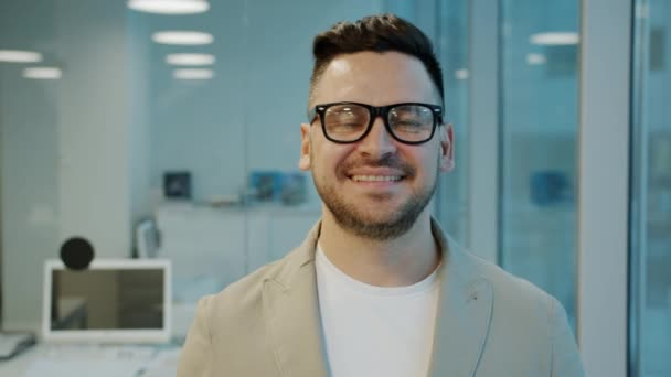 Portrait of successful young businessman in glasses smiling looking at camera in office
