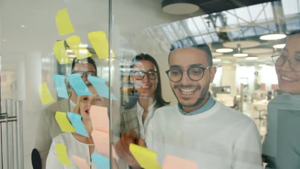 Arab businessman using glassboard with sticky notes sharing ideas with coworkers clapping hands
