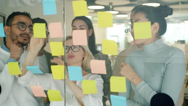 Kolegové multiraciální tým pracující s lepkavými poznámkami na skle zaneprázdněn řešením problémů