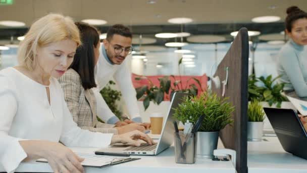 Slow motion of multi-ethnic team working in open space office talking using computers
