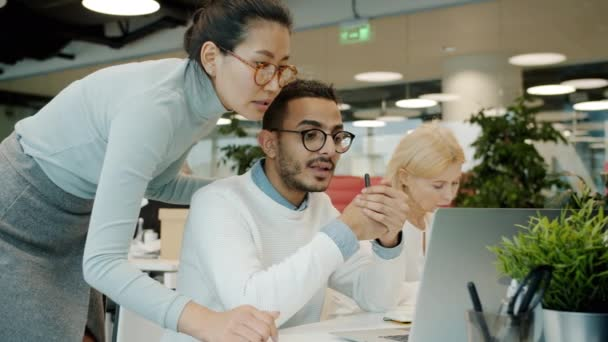 Male and female colleagues talking looking at laptop indoors in shared office