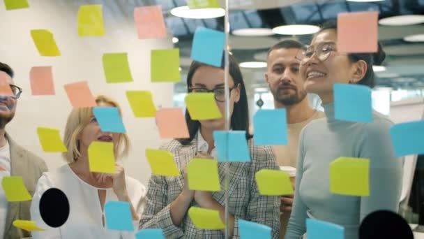 Multietnická skupina lidí používající lepicí poznámky na tabuli diskutující o podnikání v práci