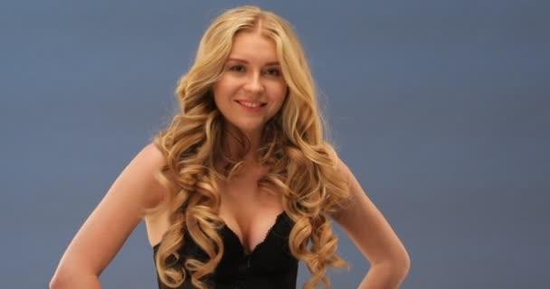 Gömbölyű szexi szőke nő gyönyörű hosszú göndör haja fekete melltartó pózol