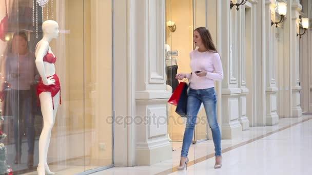 Fiatal nő, néhány séta a mall bevásárló táskák