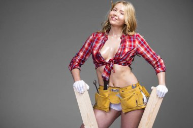 Sexy blonde woman holding building boards