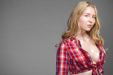 Sultry and very sexy blonde in a red plaid shirt