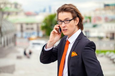 Young successful businessman calling by phone