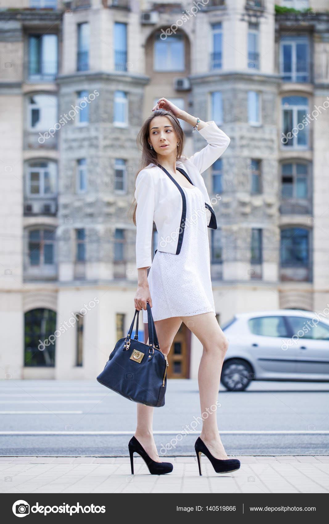 709fd444d781 Giovane bella donna castana in vestito bianco che cammina su str– immagine  stock