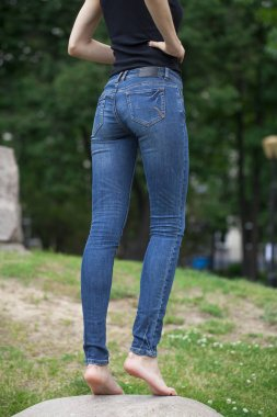 Back view of a long women legs posing with jeans