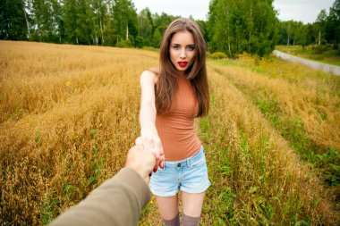 Beautiful sexy young woman holds the hand of a man in a wheat fi