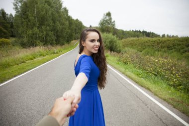 Beautiful sexy young woman holds the hand of a man