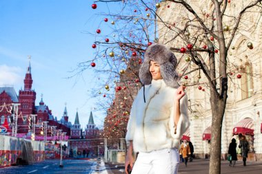 Young beautiful woman in white short mink coat