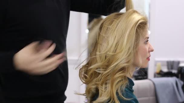 Úprava vlasů v salonu krásy. Krásná blondýnka v kadeřnictví