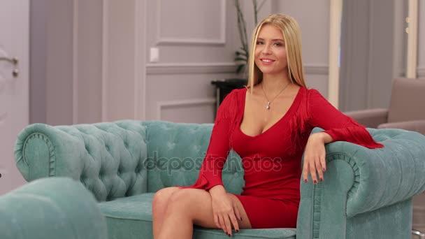 Okouzlující sexy blondýna v červených šatech sedí na tyrkysové rozkládací v salonu krásy