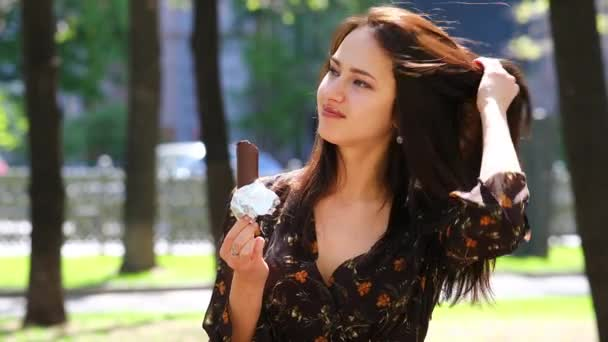 Eskimo. Mladá bruneta žena jíst na zmrzliny, horké léto venku