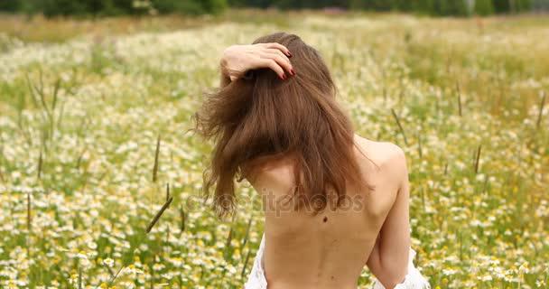 Krásná mladá bruneta dívka pózuje na pozadí heřmánkem glade