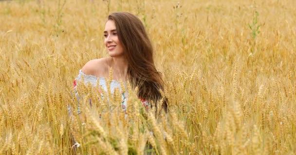 junges schönes Mädchen posiert vor einem Weizenfeld Hintergrund