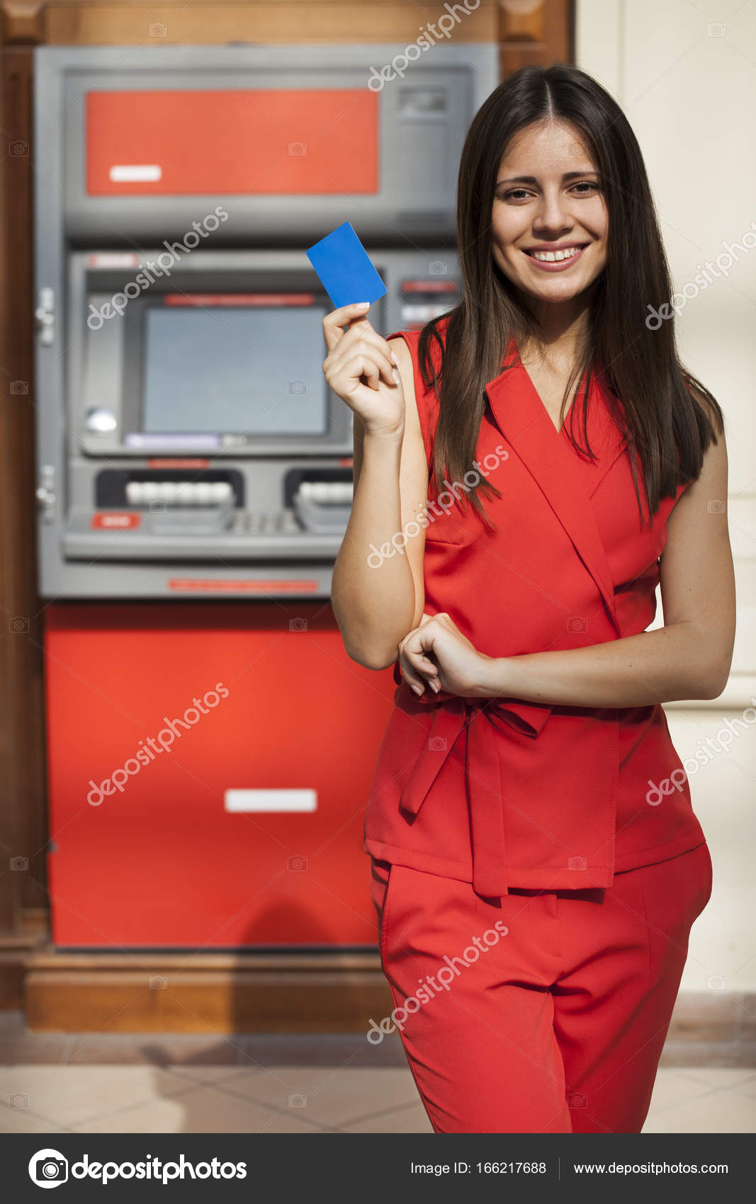 020056f089ff Young happy brunette woman in red dress withdrawing money from credit card  at ATM — Photo by ...