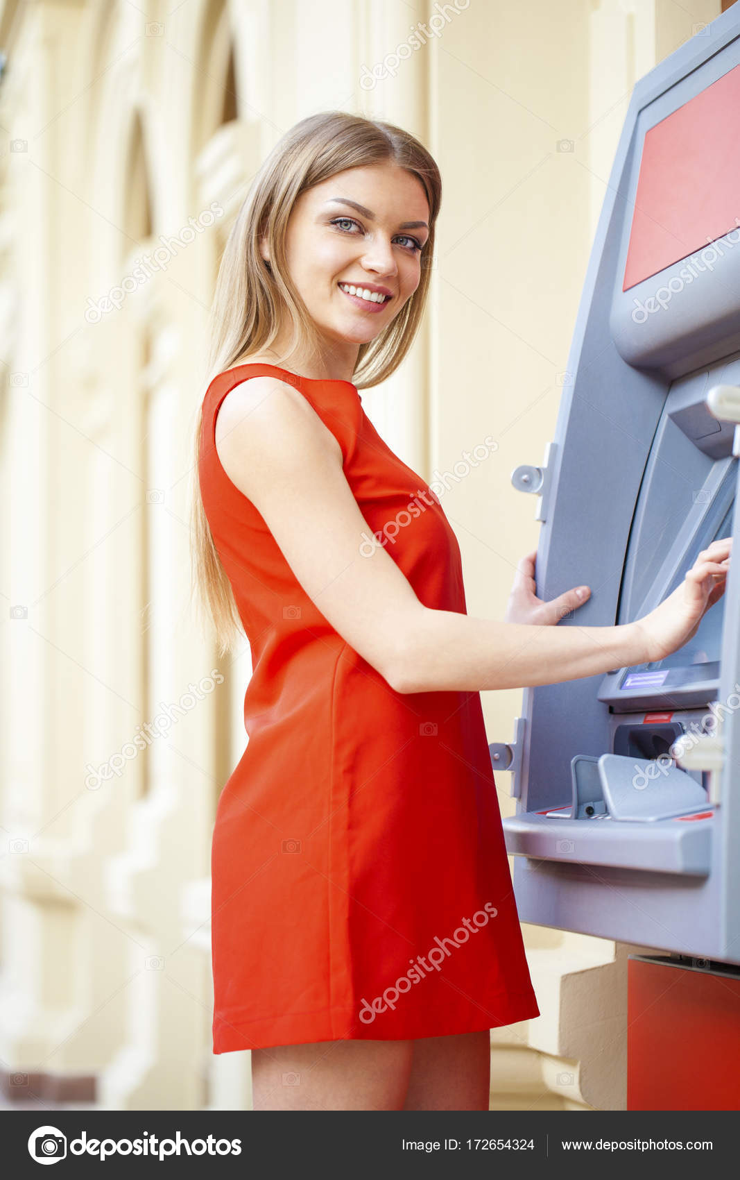 e57c8a543c0c Young happy blonde woman in red dress withdrawing money from credit card at  ATM — Photo by ...