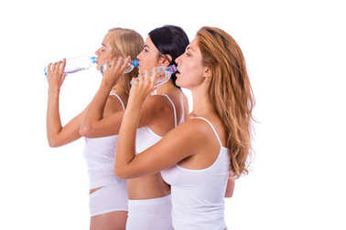 Fitness women. Three young beautiful girlfriends drinking water