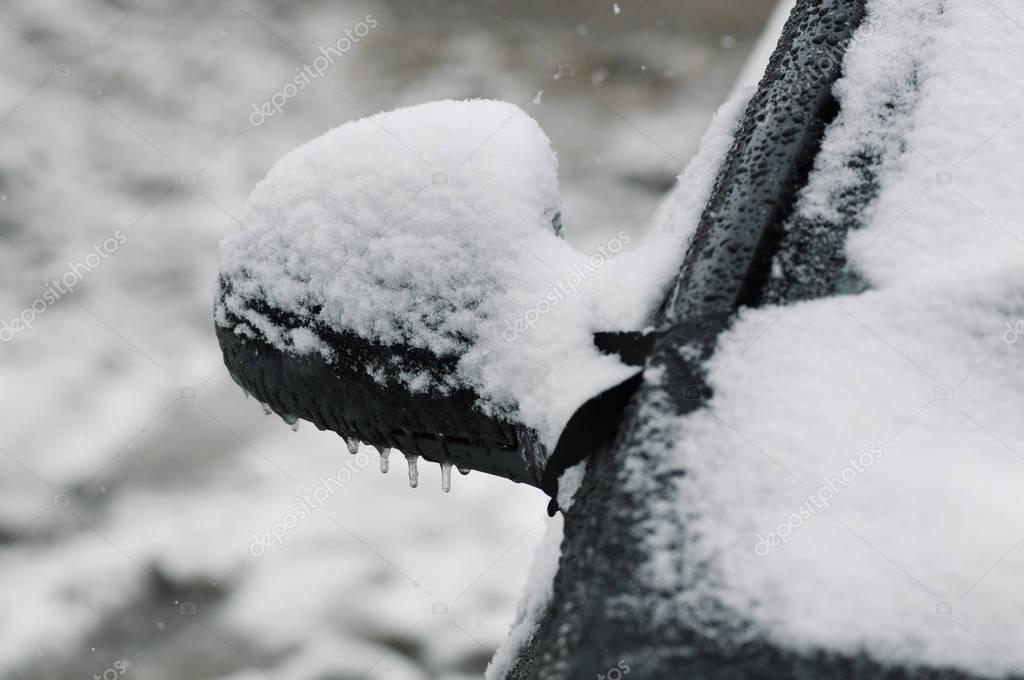 Black car side mirror covered in snow