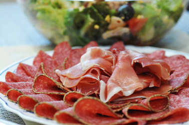 Meat plate with thinly sliced salami and jamon with a bowl of salad on the background