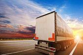 Velké semi truck s bílým přívěsu na venkovské cestě proti obloze krásný západ slunce