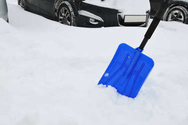 Blue shovel in snow against cars on parking