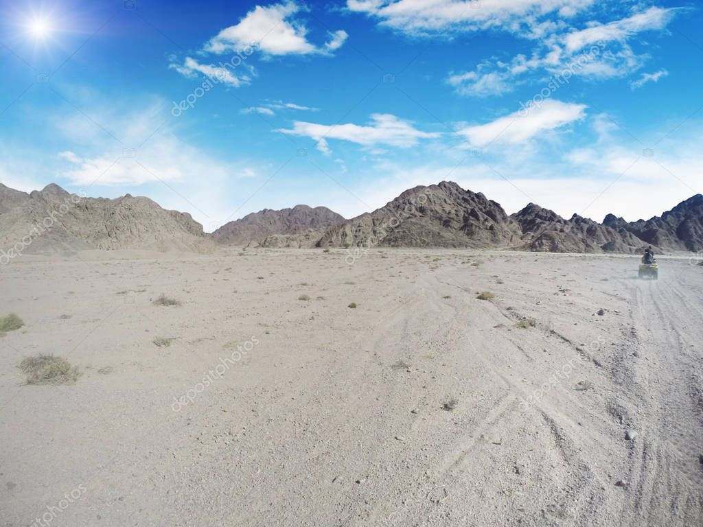 Quad bike in the sand desert with mountains against blue sky with clouds and sun