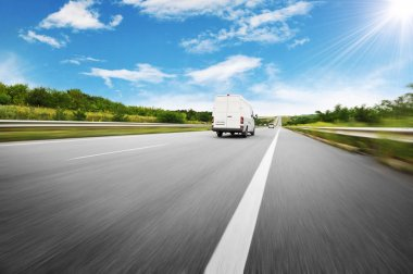 Big white van in motion on the countryside road shipping goods against blue sky with sun