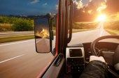 Fotografie Řídicí panel náklaďák s řidiči rukou na volantu a boční zrcátka na venkovské cestě proti noční obloze s západ slunce