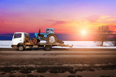 White tow truck with old blue tractor on the winter countryside road against night sky with sunset