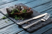 Roasted meat with green dill, peppercorns, silver fork and knife on a board and blue wooden background