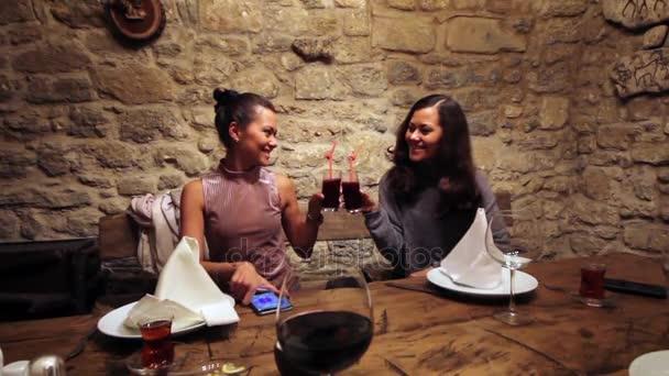 Due sorelle celebrando una riunione in un caffè con succo di gemelli