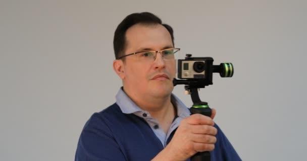Filmaře drží mobilní akční kameru na prstenec