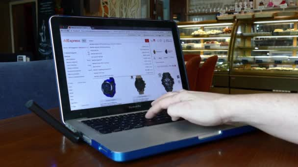 Muž navštíví aliexpress web pomocí pc notebooku Macbook Pro v kavárně