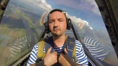 Man in the cockpit of an airplane carrying an aerobatics figure