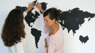 The journalist is reporting on the background of a large map of the world in front of the camera.