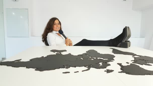 Girl with microphone sits in the office on the background of the world map with her legs on the table.