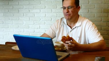 Man drinking tea in cafe with laptop at the table
