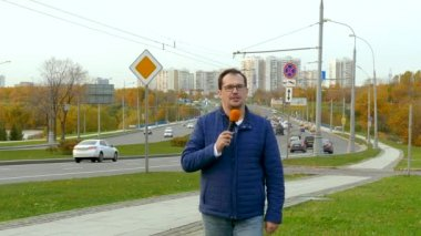 Journalist is reporting from the road for television with breaking news