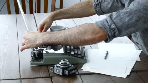 Spisovatelé ruce na vinobraní stroji v bílé místnosti
