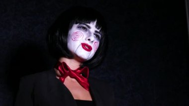 Close up portrait of Young woman in horror, hallowing style make up sings a song on dark background.