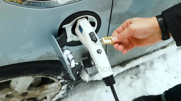 Environmentally conscious male charging electric vehicle at winter time.