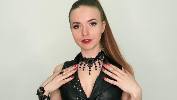 Szép szőke lány egy fekete bőr ruha a drága ékszerek. Bőrből készült szexi ruha