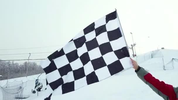 Mann mit Zielflagge auf Skipiste