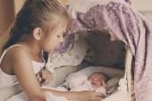 Holčička se dívá na novorozené dítě v postýlce