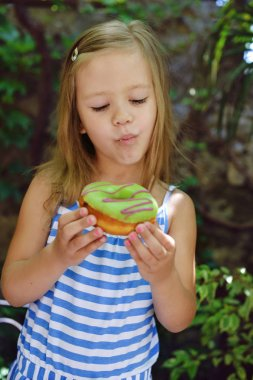 Cute little girl eating sweet donuts outdoors