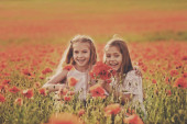 Két boldog lány nevet a mákmezőn.